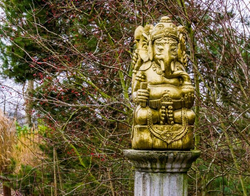 Goldene Ganesha-Skulptur auf einem Steinpfosten, geistige Dekorationen für den Garten, Elefantgott von Indien lizenzfreies stockfoto