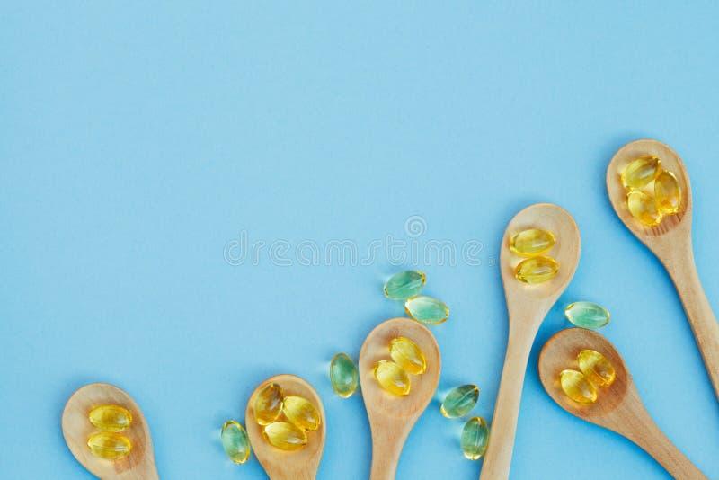 Goldene gelbe Fischölkapseln in den hölzernen Löffeln lokalisiert auf blauem Hintergrund stockfotos