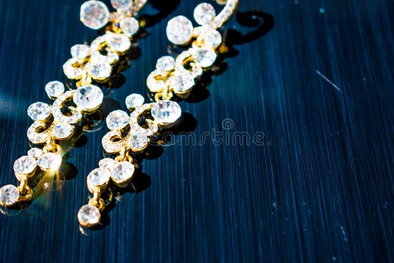 Goldene, gelbe Ohrringe auf den Ohren Glättung und elegante Dekorationen mit den großen und kleinen weißen Steinen lizenzfreies stockfoto