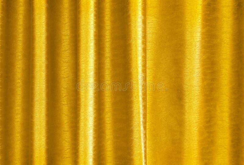 Goldene gelbe Seidenvorhangluxusbeschaffenheit für Hintergrund- und Entwurfskunstwerk stockfotos