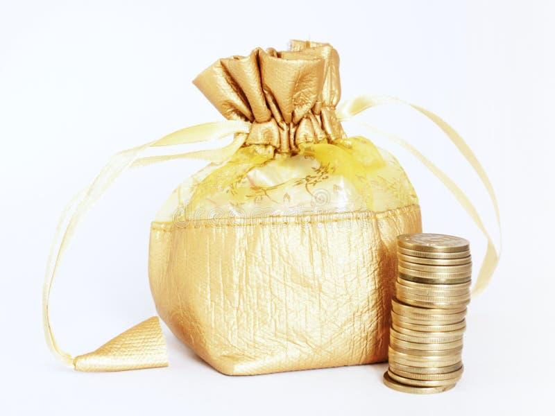 Goldene Geld-Tasche mit Stapel Goldmünzen lizenzfreie stockfotografie