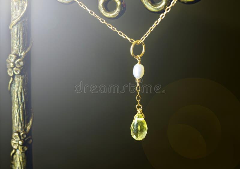 Goldene Halskette mit Zitronenquarz oder gelbem Quarz mit weißer Perle auf schwarzem Hintergrund stockfotos