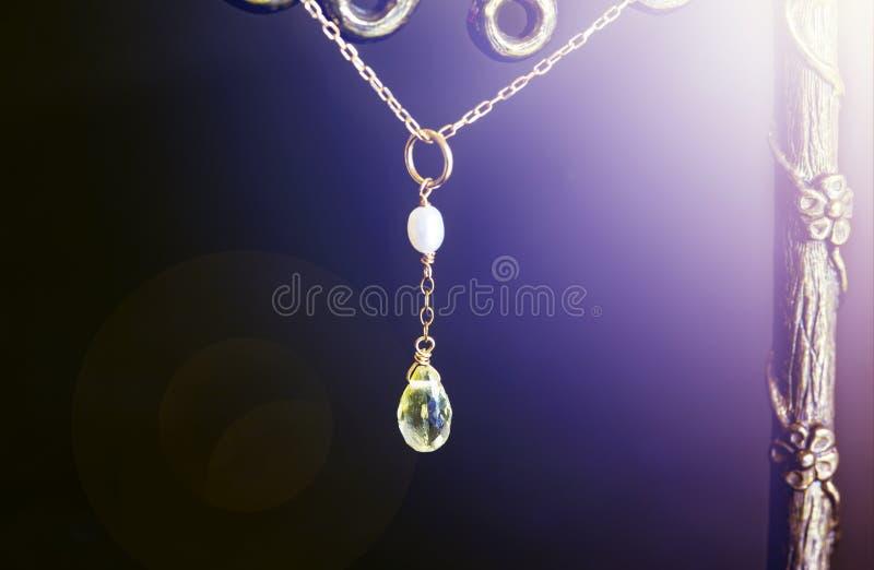 Goldene Halskette mit Zitronenquarz oder gelbem Quarz mit weißer Perle auf schwarzem Hintergrund lizenzfreie stockfotografie