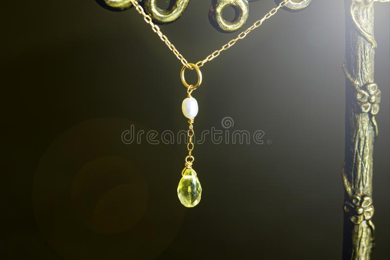 Goldene Halskette mit Zitronenquarz oder gelbem Quarz mit weißer Perle auf schwarzem Hintergrund lizenzfreie stockfotos