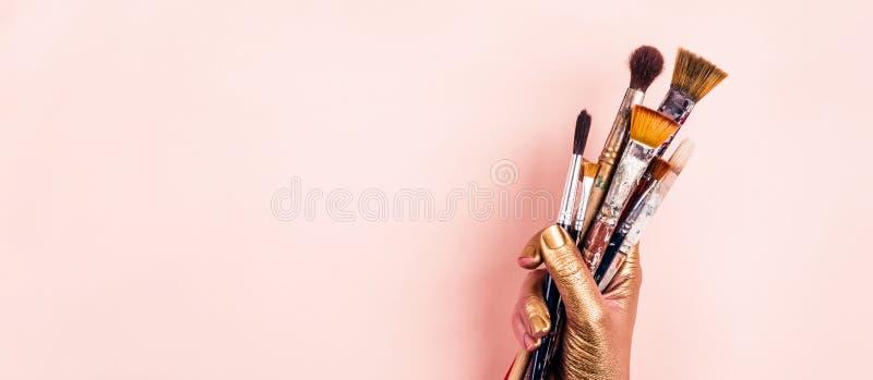Goldene Hand des weiblichen Künstlers mit Satz Bürsten Nette empfindliche Pastellfarben lizenzfreie stockfotos