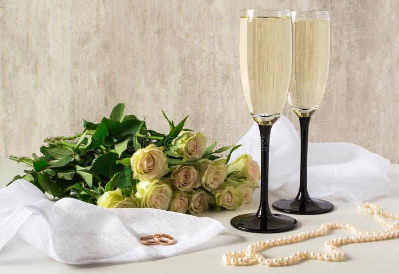 Goldene Hochzeits-Ringe Zwei Gläser der Champagner- und Perlenhalskette stockbild