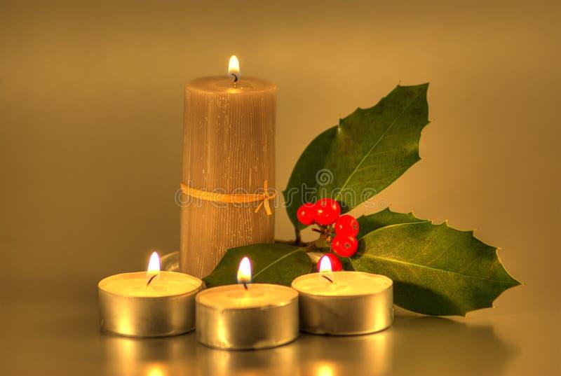 Goldene Kerzen mit Stechpalme lizenzfreie stockfotos