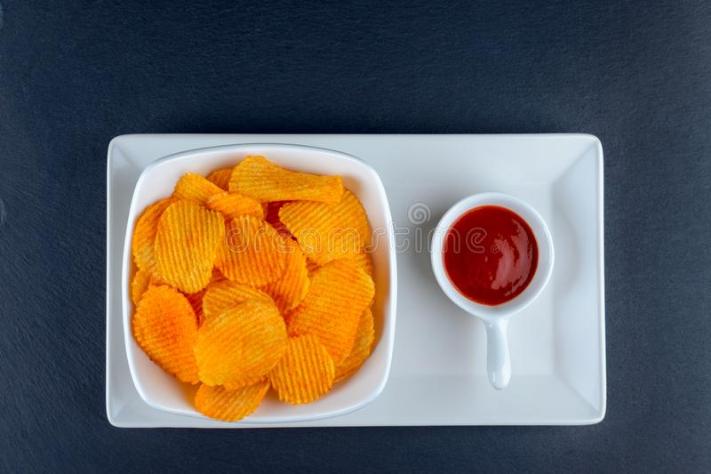 Goldene knusprige Kartoffelchips in einer Schüssel mit souce, flache Lage stockfotografie