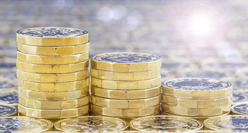 Goldene Münzen in drei Abstiegstapeln mit Lichteffekten stockbilder