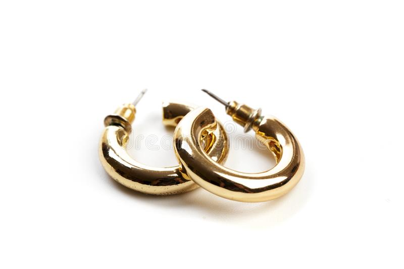 Goldene Ohrringe lokalisiert auf weißem Hintergrund - Bild stockbild