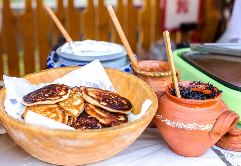 Goldene Pfannkuchen in einer hölzernen Schüssel in einer rustikalen Art Beläge für Pfannkuchen in den keramischen Töpfen stockbilder