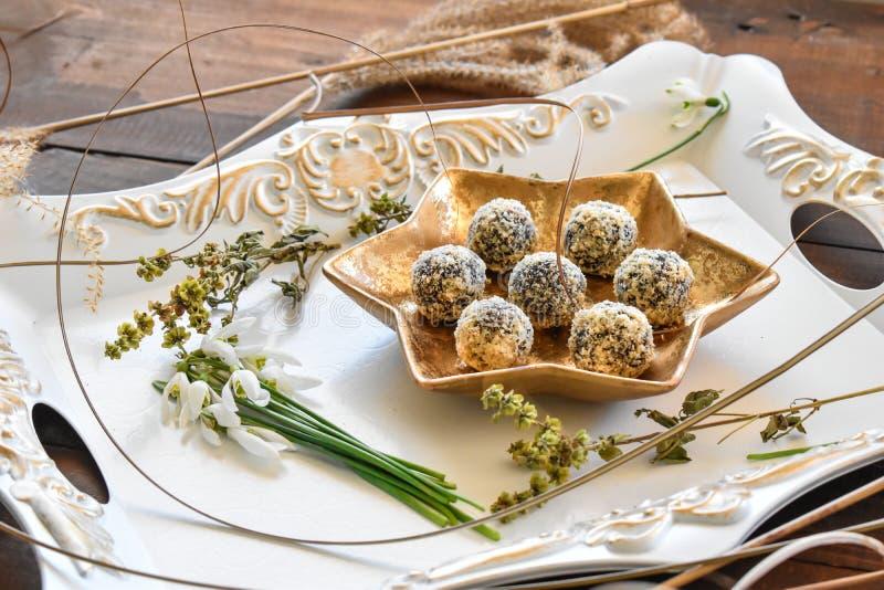 Goldene Platte mit datepalm und Walnussschokoladenbällen lizenzfreie stockfotos