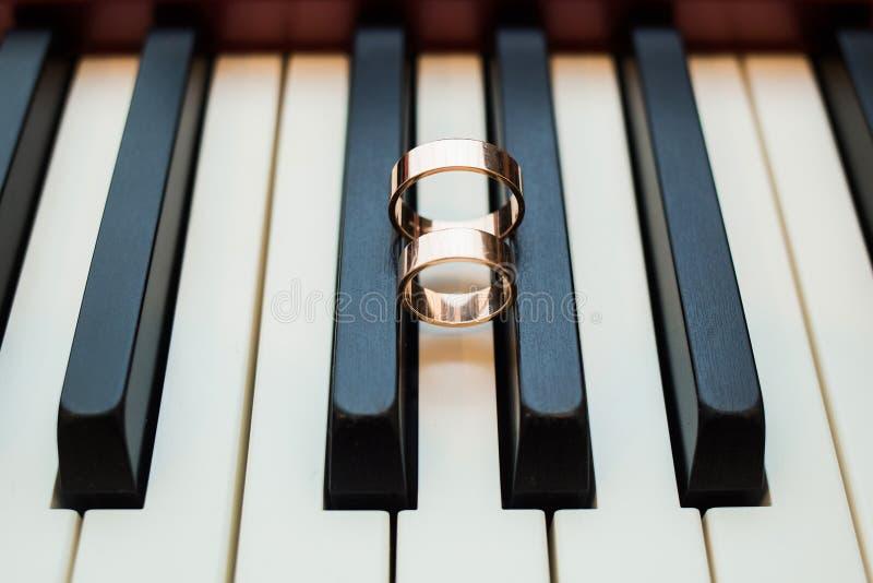 Goldene Ringe der glänzenden Hochzeit auf Schwarzweiss-Schlüsseln des Klaviers lizenzfreies stockbild