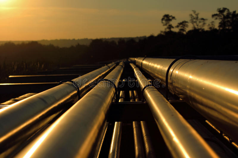Goldene Rohrleitungsverbindung vom groben Ölfeld stockfotografie