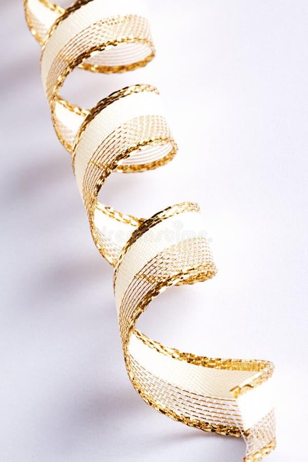 Goldene Rotationfarbbänder auf weißem Hintergrund stockbild