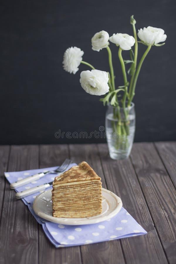 Goldene russische Pfannkuchenserviette mit dunklem Hintergrund Ranunkulyus-Butterblumeblumenstrauß stockbild