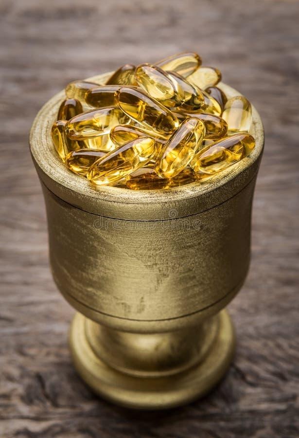 Goldene Schüssel mit goldenen Diätpillen Vitamin E lizenzfreie stockbilder