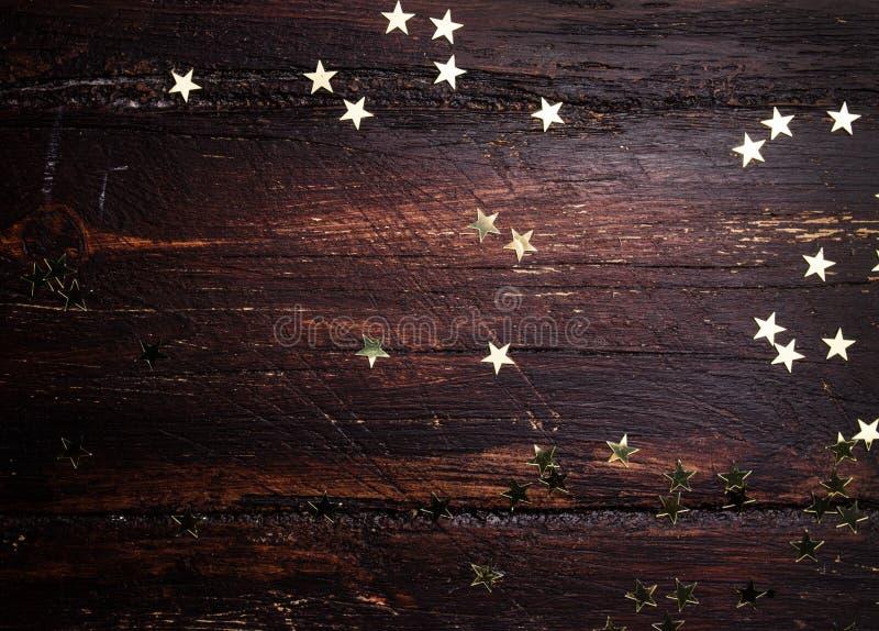 Goldene Sterne des Funkelns auf Schmutzholzhintergrund lizenzfreie stockbilder