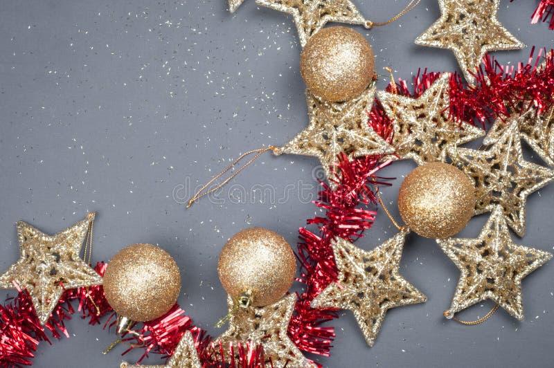 Goldene Sterne Weihnachtszusammensetzungsdekorationen auf einem grauen Hintergrund mit rotem Lametta lizenzfreie stockfotos