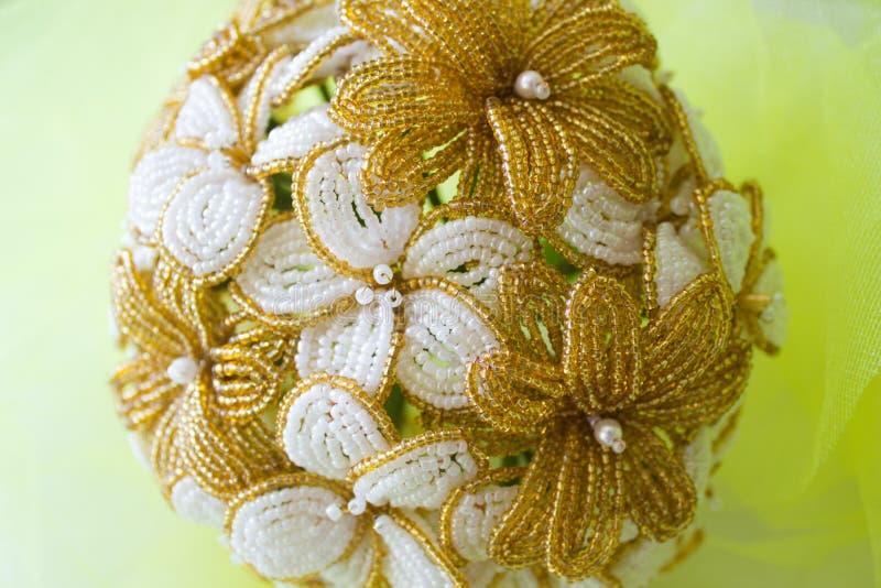 Goldene und wei?e Blumen des Heiratsblumenstrau?es von den Perlen Auf einem gelben unscharfen Hintergrund lizenzfreie stockfotografie