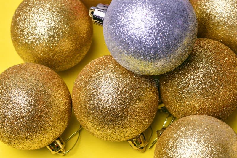 Goldene Weihnachtsballspielwaren liegen auf einem gelben Hintergrund und einem Ball von silbernen Farblügen auf die Oberseite lizenzfreies stockbild