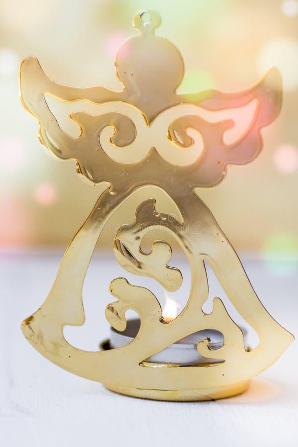 Goldene Weihnachtsengelszahl, brennende Kerze, bunte Konfettis beleuchtet im Hintergrund, festliche Atmosphäre, Grußkarte lizenzfreies stockbild