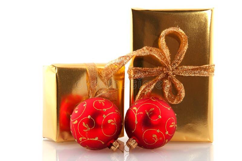 Goldene Weihnachtsgeschenke mit roten Kugeln stockfotografie