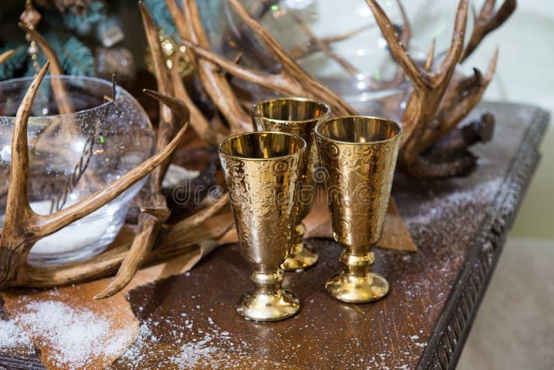 Goldene Weingläser des Weihnachtsdekorationsdekors drei ohne Getränke auf einem Holztisch im künstlichen Schnee stockfotografie