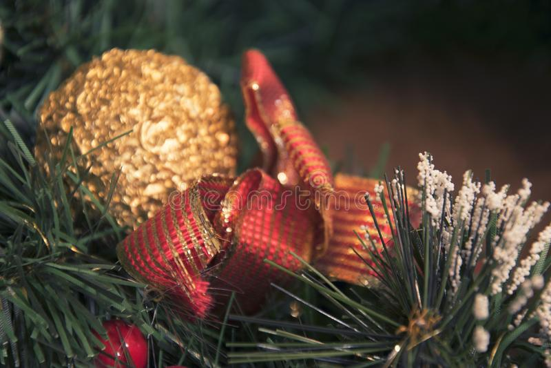 Goldener Ball und rotes Weihnachtsband in einem Baumast lizenzfreies stockbild