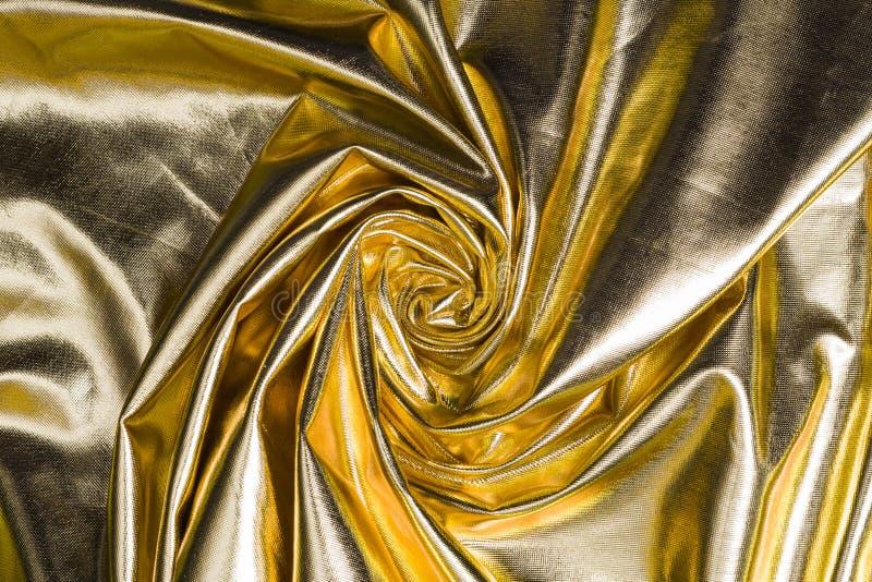 Goldener Beschaffenheitssatin, verdreht in gewundenen Hintergrund lizenzfreies stockfoto