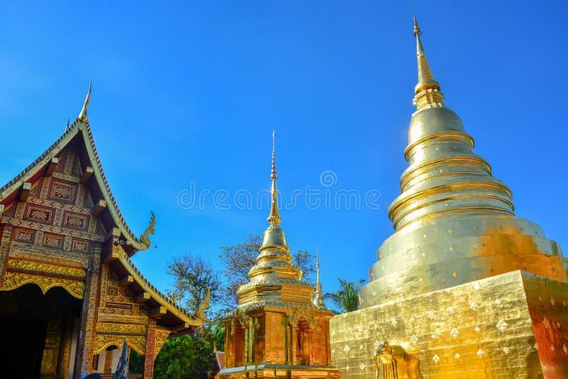 Goldener buddhistischer Tempel, glänzende goldene Pagode und hölzerne Kirche bei Wat Pra Sing mit Hintergrund des blauen Himmels, lizenzfreies stockfoto