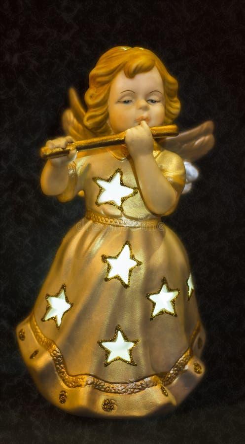 Goldener Engel, der auf Flöte spielt stockbild