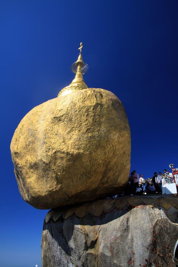 Goldener Felsen, der gegen blauen Himmel kontrastiert Gold gemalter Flussstein, der am Rand des steilen hohen Berges balanciert stockbild