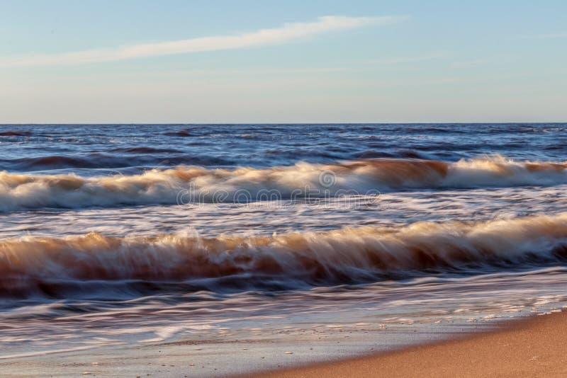 Goldener gelber schäumender Meereswellenhintergrund bei romantischem Strandsonnenuntergang mit endlosem Horizont stockfotografie