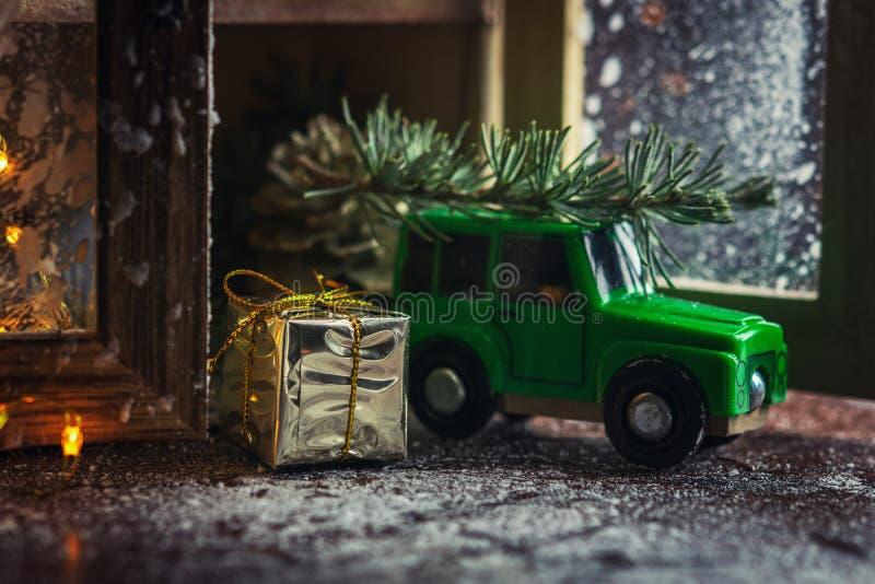 Goldener Geschenkbox- und Weihnachtsdekorationsgegenstand mit dem grünen Spielzeugauto, das einen Weihnachtsbaum auf hölzerner Ta lizenzfreies stockbild