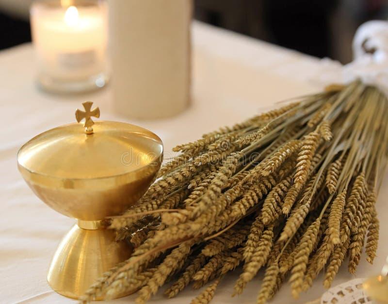 Goldener Kelch und die Ohren des Weizens über einem Altar in der Kirche stockfotografie
