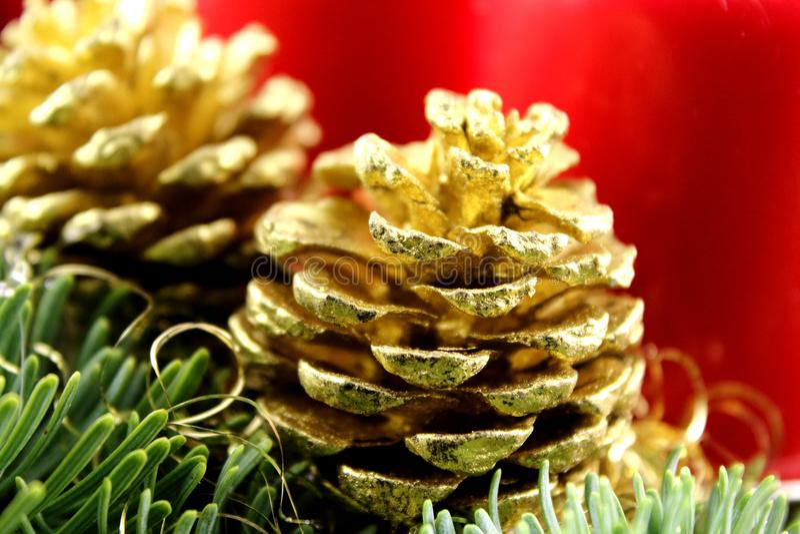 Goldener Kiefernkegel auf einer Weihnachtsdekoration mit Tanne und roten Kerzen stockfotografie