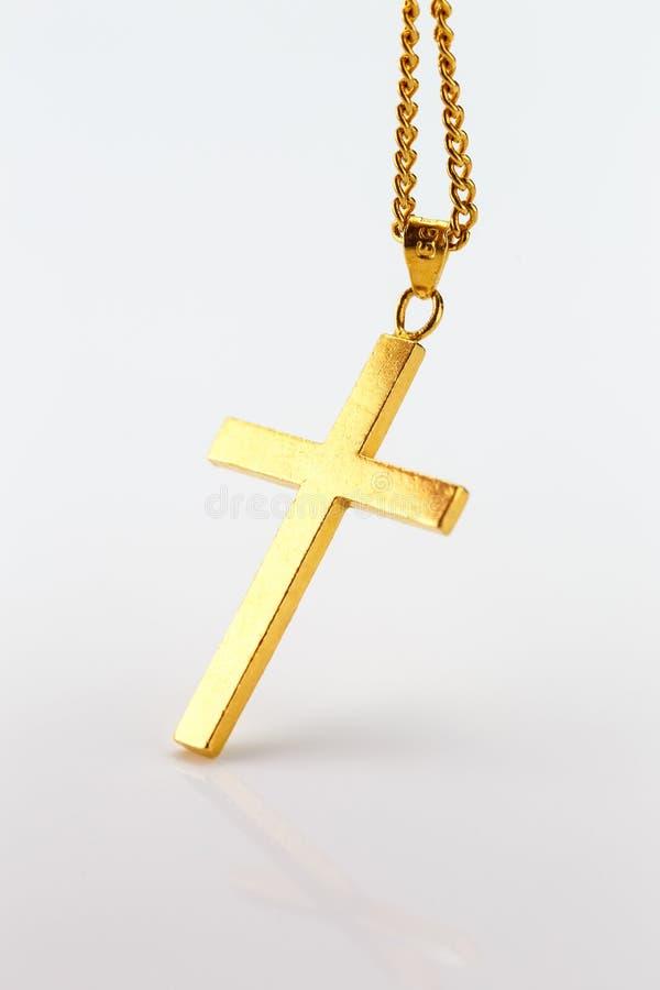 Goldener Kreuzanhänger auf der Goldkette auf weißem Hintergrund stockfotografie