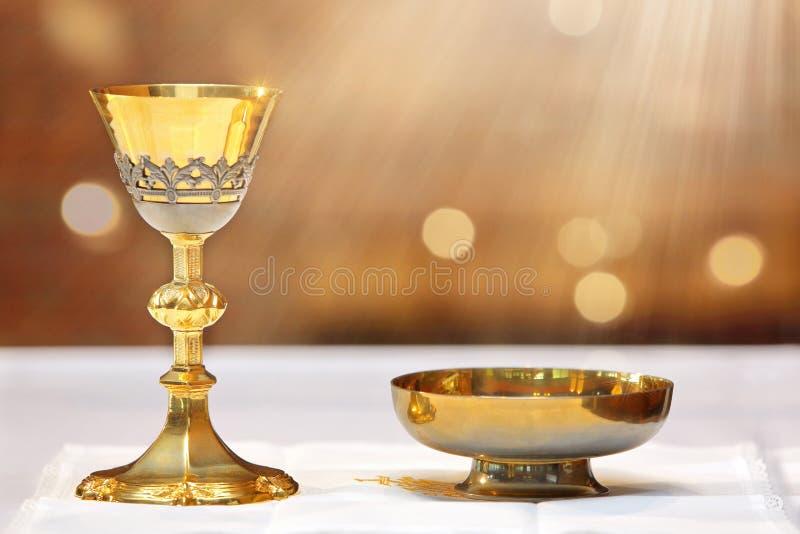 Goldener Messkelch auf dem Altar und den Strahlen des Lichtes vom Himmel stockfoto