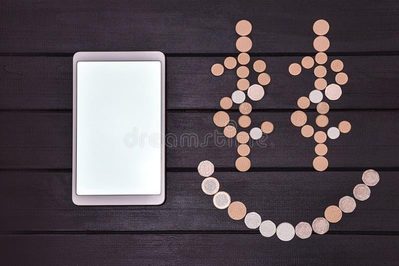 Goldener Pfeil und das Diagramm der M?nzen Smartphone und Münzen bildeten ein Smiley Face-emoji auf dem Tisch Gl?cklicher Tag Erf stockfotografie