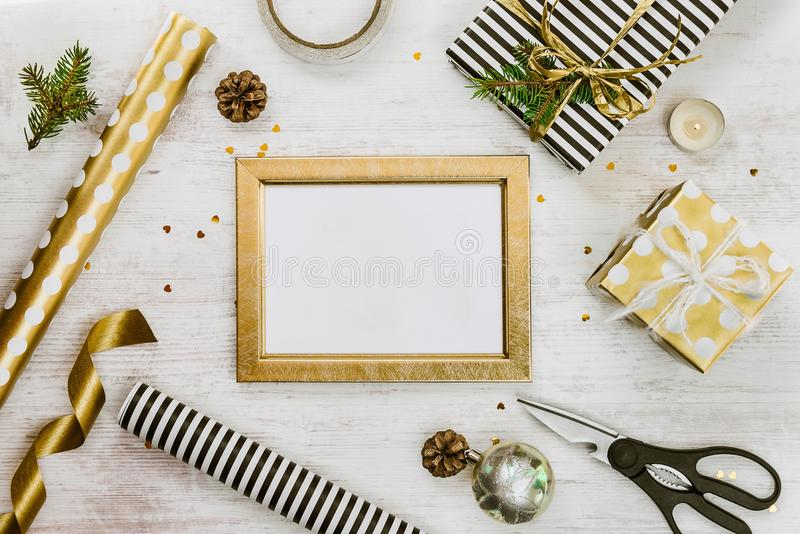 Goldener ptoto Rahmen, Geschenkboxen, Kiefernkegel und Weihnachtsspielwaren und Verpackungsmaterial auf einem weißen hölzernen al lizenzfreies stockfoto