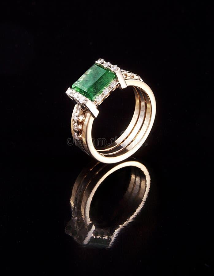Goldener Ring mit dem Smaragddiamanten glänzend stockfotografie