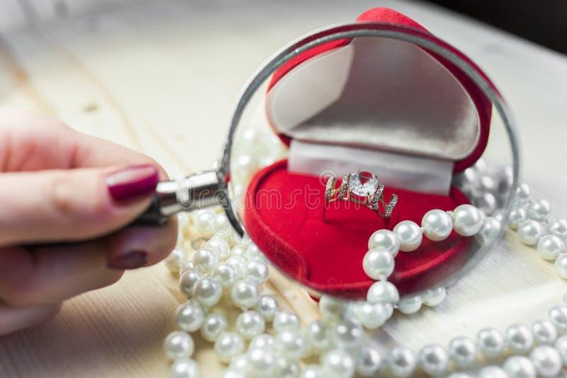 Goldener Ring mit Topas in einer roten Geschenkbox mit Perlen am Rand der Tabelle stockbild