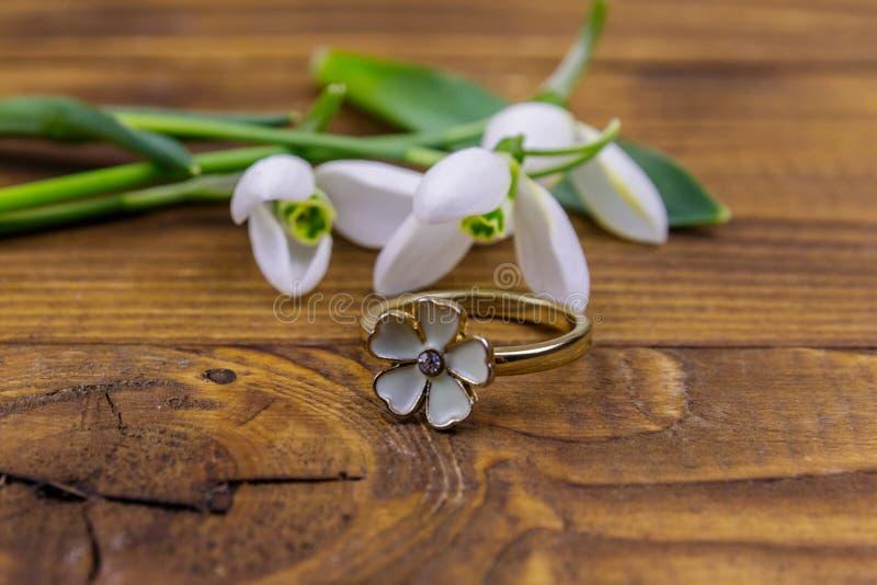 Goldener Ring und Schneetropfen auf Holzboden lizenzfreies stockbild