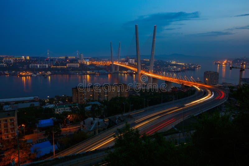 Goldener Schr?gseilbr?ckestra?en-Autoverkehr von oben Moderne Nachtbeleuchtung Wladiwostoks Russland stockbilder
