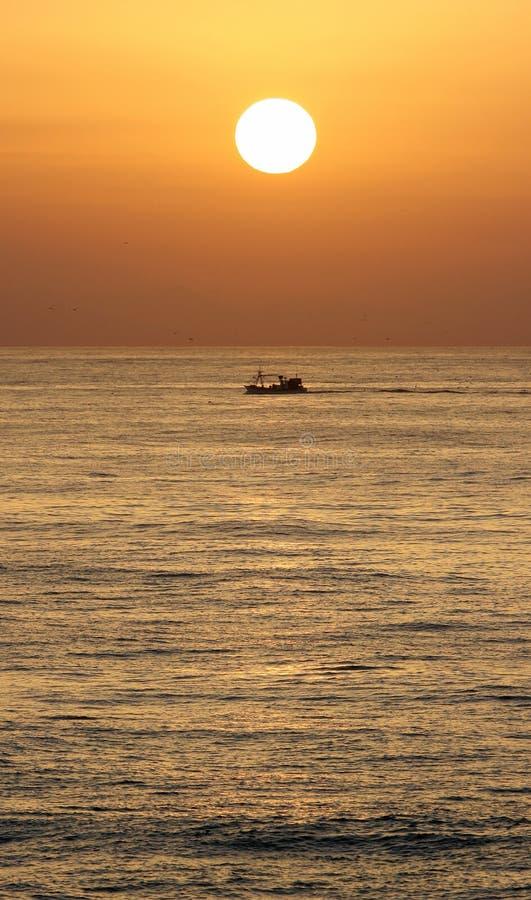 Goldener Sonnenaufgang in Marbella, in Südspanien mit Ozean und Boot stockfotografie