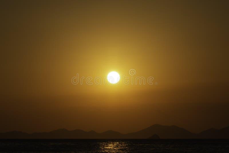 Goldener Sonnenuntergang über dem Meer, Gebirgslinien am Hintergrund Achtzig Prozent Kopienraum im Bild stockfotos