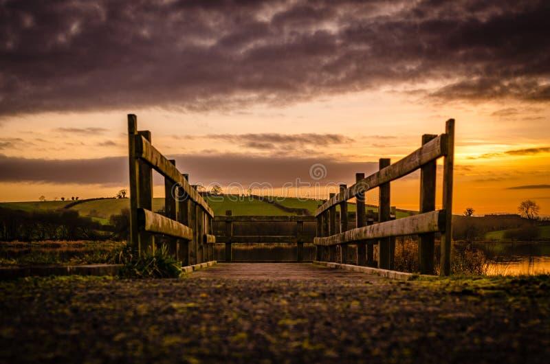 Goldener Sonnenuntergang auf einem hölzernen Gehweg stockfoto