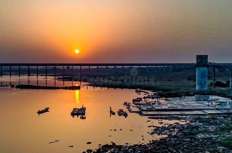 Goldener Sonnenuntergang mit Fluss u. Brücke lizenzfreies stockbild