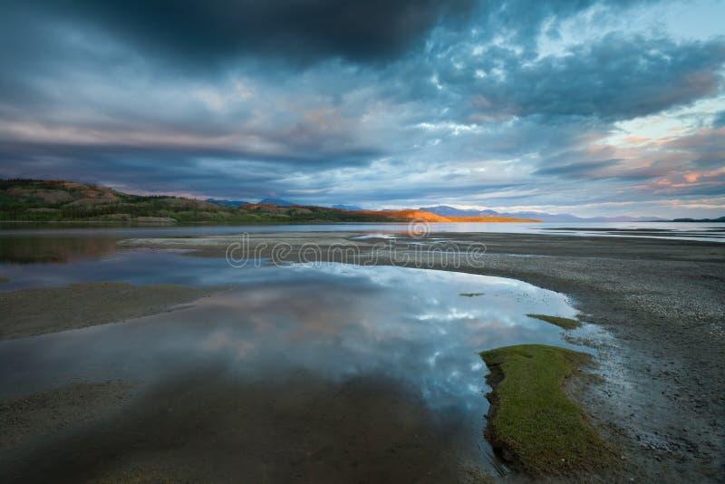 Goldener Sunbeam und drastischer Himmel in See Laberge lizenzfreie stockfotos